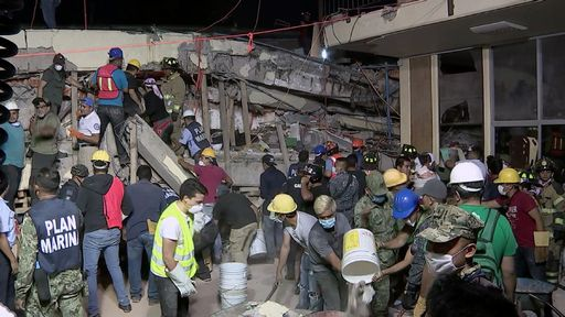 """This TV grab taken from the Mexican Presidency shows rescue teams looking for people trapped in the rubble at the Enrique Rebsamen elementary school in Mexico City on September 19, 2017.  At least 21 children were killed at the Enrique Rebsamen elementary school that collapsed in the Mexican capital and rescue efforts were still underway said Mexican President Enrique Pena Nieto, after a powerful earthquake rattled the area.  / AFP PHOTO / Mexican Presidency / STR / RESTRICTED TO EDITORIAL USE - MANDATORY CREDIT """"AFP PHOTO / Mexican Presidency"""" - NO MARKETING NO ADVERTISING CAMPAIGNS - DISTRIBUTED AS A SERVICE TO CLIENTS"""